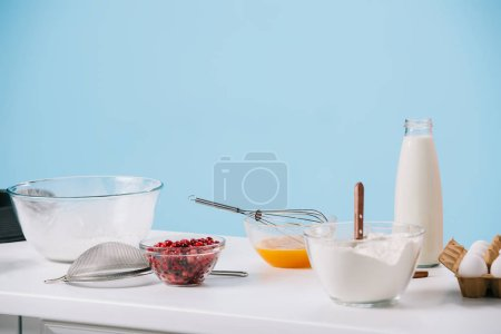 Photo for Various cooking utensils and products on white kitchen table isolated on blue - Royalty Free Image