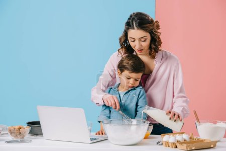 Photo for Cute little boy looking at laptop display while mother cracking walnut on bicolor background - Royalty Free Image