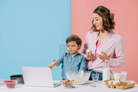 Photo for Little boy pointing at laptop display while cooking with mother on bicolor background - Royalty Free Image