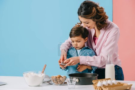 Photo for Pretty mother with cute little son cracking walnuts while cooking together on bicolor background - Royalty Free Image
