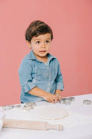 Photo pour Mignon petit garçon chiffres de coupe dans la pâte avec des moules à pâte isolés sur rose - image libre de droit
