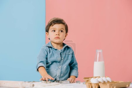 Photo for Little kid cutting figures in dough at white kitchen table on bicolor background - Royalty Free Image