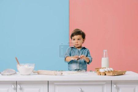 Photo pour Mignon petit garçon à table de cuisine blanche avec les ingrédients et ustensiles sur fond bicolore - image libre de droit