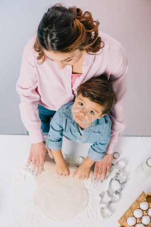 Photo for Top view of mother with little son rolling out dough at kitchen table together on light background - Royalty Free Image