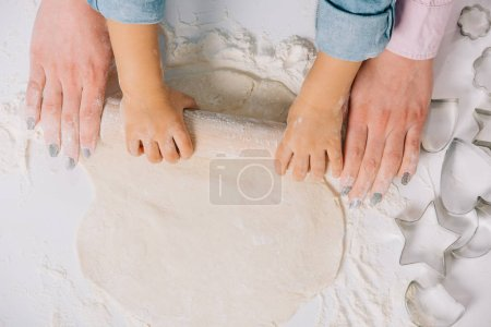 Photo for Cropped view of mother and child rolling out dough together on white background - Royalty Free Image
