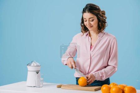 Photo pour Orange coupe jolie femme sur planche à découper en bois isolée sur bleu - image libre de droit
