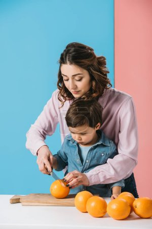 Photo for Mother with cute little son cutting oranges together on bicolor background - Royalty Free Image