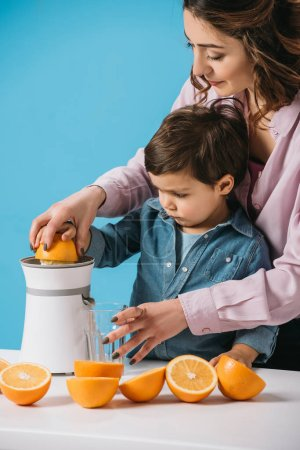 Photo for Cute little boy squeezing fresh orange juice on juicer together with mother isolated on blue - Royalty Free Image