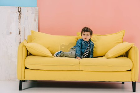 Photo for Cute little boy in blue jacket and green jeans sitting on yellow sofa - Royalty Free Image