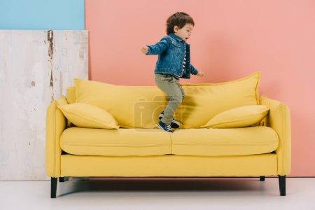 Foto de Niño lindo en chaqueta azul y pantalones vaqueros verdes saltando sobre el sofá amarillo - Imagen libre de derechos