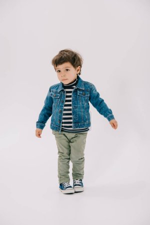 Photo for Adorable little boy in blue jacket and green jeans isolated on white - Royalty Free Image