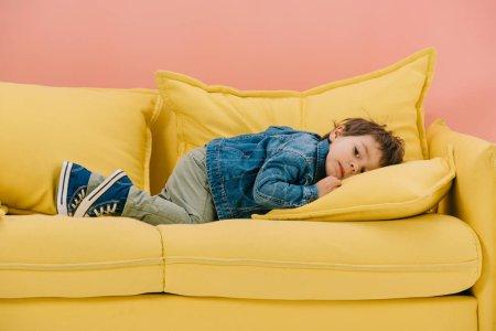 Photo pour Mignon petit garçon en veste de coton bleu et jean vert posé sur canapé jaune - image libre de droit
