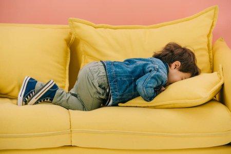 Photo pour Mignon petit garçon couché le visage sur un canapé confortable jaune - image libre de droit