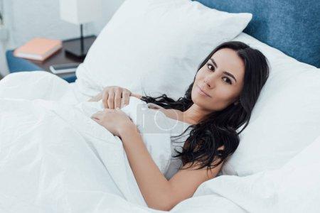 Photo pour Belle femme brune, couché dans son lit avec le sourire - image libre de droit