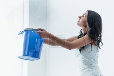Photo pour Confus jeune femme tenant seau bleu sous les gouttes d'eau - image libre de droit