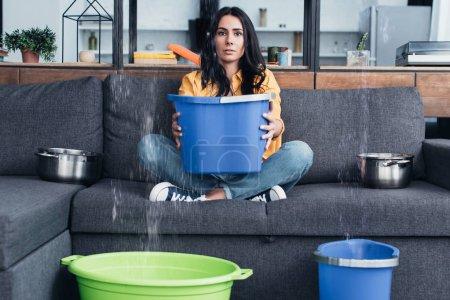 Photo pour Brunette femme tenant seau sur le canapé pendant les dégâts d'eau dans le salon - image libre de droit
