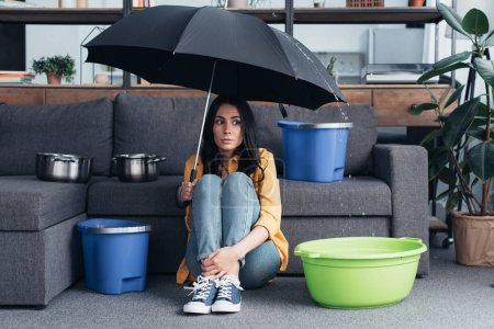 Photo pour Fille confus assis sous le parapluie dans le salon - image libre de droit