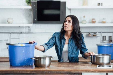 Photo pour Femme brune confus traitant des dégâts d'eau dans la cuisine - image libre de droit