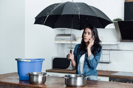 Photo pour Femme choquée avec parapluie traitant des dégâts d'eau dans la cuisine et parlant sur smartphone - image libre de droit