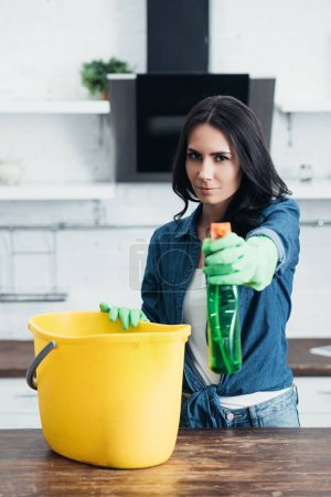 Photo for Confident woman in rubber gloves holding spray and bucket in kitchen - Royalty Free Image