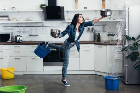 Photo pour Vue complète de la femme enfoncée dans un jean traitant de la fuite d'eau dans la cuisine - image libre de droit