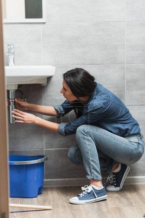 Photo pour Brunette femme en jeans fixation pipe dans la salle de bain - image libre de droit