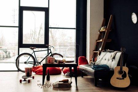 Foto de Mesa de centro con comida y bebidas junto a la guitarra acústica y sofá en salón desordenado - Imagen libre de derechos