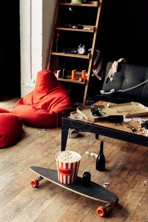 Photo pour Planche à roulettes avec boîte à pop-corn près de la table basse dans le salon désordonné - image libre de droit