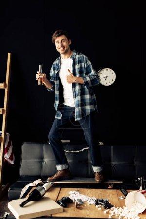 Photo pour Homme gai tenant bouteille et montrant pouce vers le haut dans le salon désordonné - image libre de droit