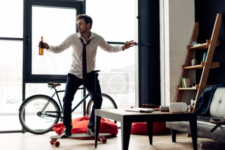 Photo for Man riding skateboard and holding drink after party at home - Royalty Free Image