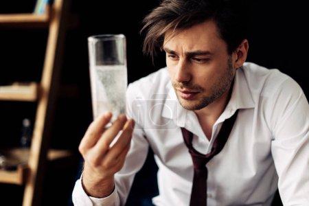 Foto de Hombre guapo busca en el vaso de agua helada después de fiesta - Imagen libre de derechos
