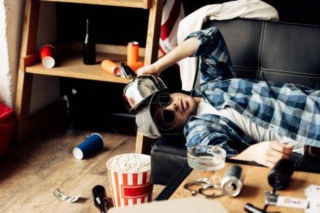 Photo pour Bel homme tenant théière près de la tête tout en étant couché sur le canapé dans le salon désordonné - image libre de droit