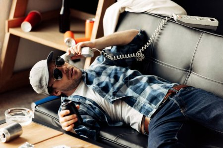 Photo for Handsome man in sunglasses and cap lying on sofa and talking on retro phone in living room - Royalty Free Image