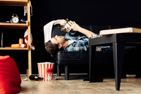 Photo for Man drinking from teapot while lying on sofa in messy living room - Royalty Free Image