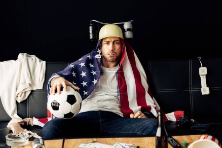Photo for Man wearing beer helmet drinking and holding football while sitting with american flag on shoulders - Royalty Free Image
