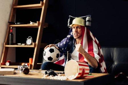Photo pour Homme portant casque boire de la bière et tient le ballon tout en sirotant un drapeau américain sur les épaules et regarder match - image libre de droit
