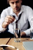 selective focus of man putting aspirin in glass of water