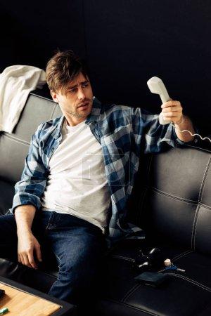 Foto de Hombre borracho mirando teléfono retro y sentado en el sofá después de fiesta en casa - Imagen libre de derechos