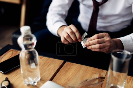 Photo for Cropped view of man holding pill in hands near bottle with water after party - Royalty Free Image