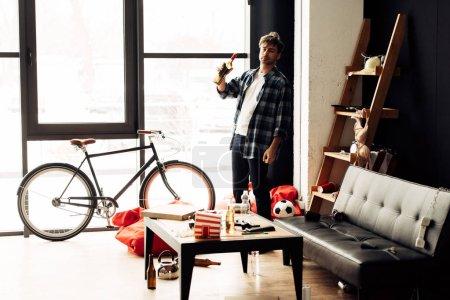 Foto de Hombre que sostiene la botella de vino en salón desordenado después de fiesta - Imagen libre de derechos