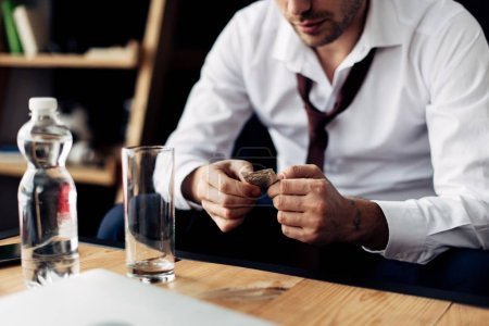 Photo for Cropped view of businessman holding pill in hands near glass of water - Royalty Free Image
