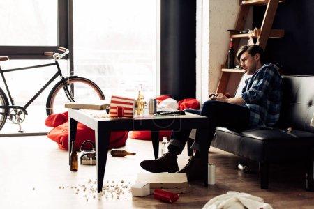 Photo pour Homme qui joue le jeu vidéo dans salon malpropre - image libre de droit