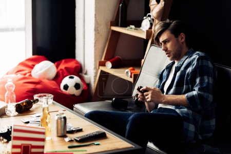 Photo for Tired man playing video game in messy living room - Royalty Free Image