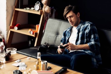 Photo for Exhausted man playing video game in messy living room - Royalty Free Image