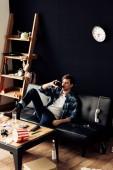 """Постер, картина, фотообои """"красивый мужчина сидит на диване и пили пиво в грязной квартиры"""""""