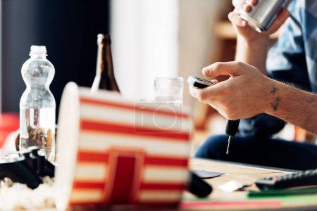 Photo pour Vue recadrée de l'homme tenant la télécommande près des boissons à la maison - image libre de droit