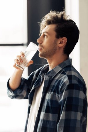 Photo for Handsome man holding glass and drinking water after party - Royalty Free Image