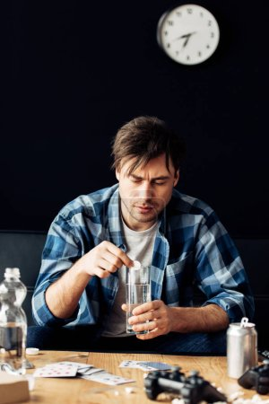 Photo for Tired man suffering from hangover holding aspirin and glass of water in hands - Royalty Free Image