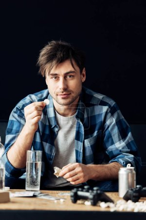 Photo for Man suffering from hangover holding aspirin and glass of water in hands - Royalty Free Image