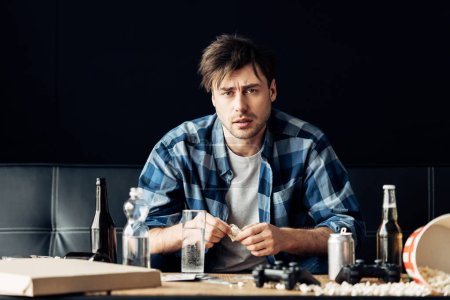 Photo for Exhausted man suffering from hangover holding aspirin and glass of water in hands - Royalty Free Image